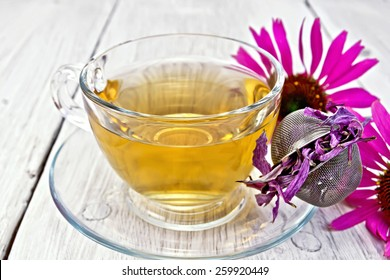 Herbal tea in a glass cup, metal sieve with dry Echinacea, fresh flowers on the background light wooden boards
