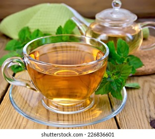 Herbal tea in a glass cup and teapot, fresh mint leaves, a napkin on a wooden boards background