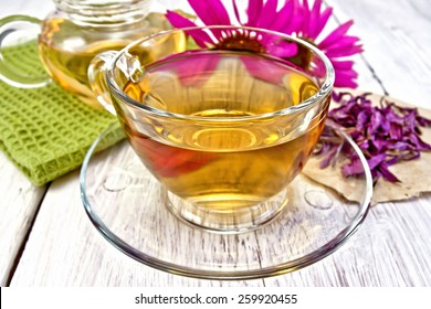 Herbal tea in a glass cup, teapot, fresh and dried flowers of Echinacea, napkin on a wooden boards background