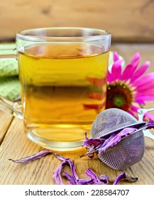 Herbal tea in a glass mug, metal sieve with dry flowers echinacea, fresh flower on the background of wooden boards
