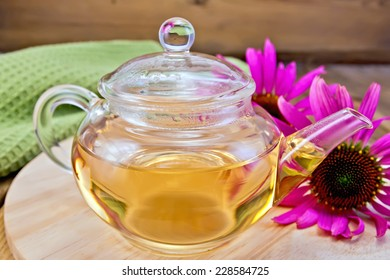Herbal tea in a glass teapot, fresh flowers echinacea, napkin on a wooden boards background