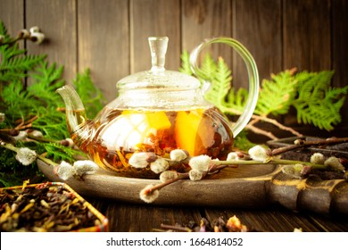 Herbal tea in a glass teapot with herbs and lemon on dark rustic background