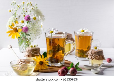 Herbal tea with herbs and flowers in a glass tea pot with honey. Bouquet of flowers on white table