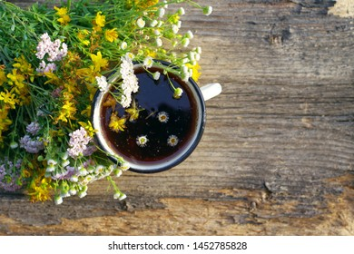 Herbal tea in an iron cup white yarrow flowers and St. John's Wort flowers on old wooden surface, top view. Tea and wild herbs, alternative medicine