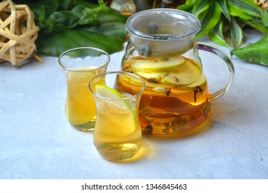 Herbal tea with juce cranberries, apple, ginger, lemon, cinnamon and thyme in a jar. Warming tea, healthy fruit infused tea. Horizontal closeup view on tropical background- Image