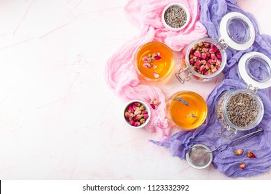 Herbal tea made from dried rose buds and lavender flowers in two transparent glass plates. Top view. Space for text.