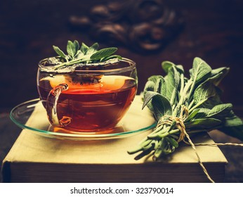 Herbal tea made from sage in glass cup standing on books, nearby lies a bundle of sage over dark wooden background. Retro toned.