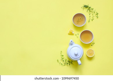 Herbal tea made of thyme and other herbs with lemon on yellow background. The view from the top. Copy space