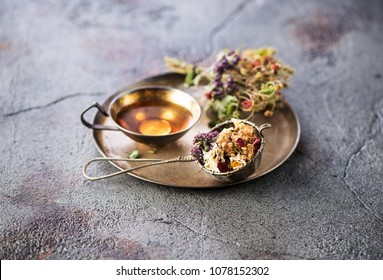 Herbal tea in a metal cup, a vintage strainer and dry medicinal herbs in a tray on a gray concrete background