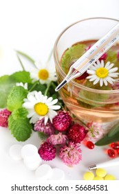 Herbal tea, pills and a thermometer- Healthcare Concept