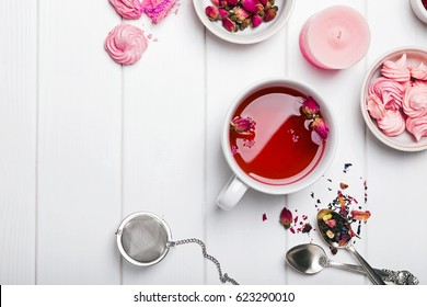 Herbal tea with roses on white wooden table, top view