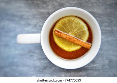 Herbal tea with a slice of lemon and a cinnamonroll