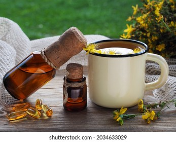 Herbal tea, tincture and extract in bottles oil in capsules and saint johns wort herb on a wooden table. Medicinal plant hypericum perforatum for use in herbal medicine, homeopathy and cosmetology