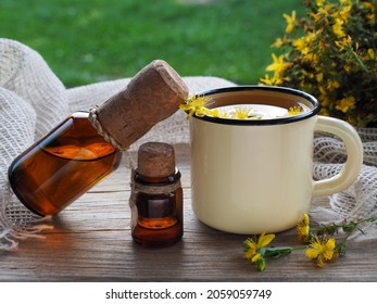 Herbal tea, tincture, oil and saint johns wort grass with yellow flowers on a wooden table, closeup. Medicinal plant Hypericum perforatum for use in herbal medicine, homeopathy and cosmetology