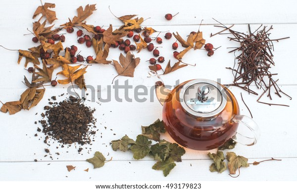 herbal tea in a transparent teapot on white wooden table