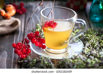 Herbal tea from the viburnum decoction of red sea buckthorn berries and thyme in a transparent glass mug in the village on a wooden table