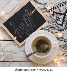 Herbal tea in white cup, blackboard with written word 'hygge', knitted blanket and small yellow lights for home decor. Hygge lifestyle concept