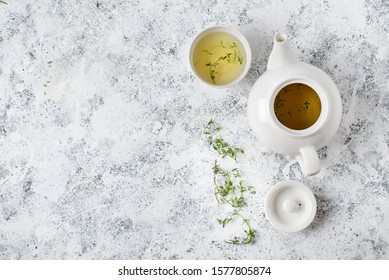 Herbal tea in white teapot and white bowl on and thyme stalks light textured background,  top view, copy space