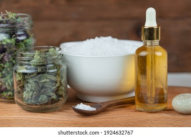 Herbal therapy, traditional medicine and homeopathy concept. Towel with salt, herbs, massage brush, candles and bottle natural organic oil essence serum.  Set for spa, massage and aromatherapy