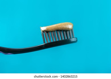 herbal toothpaste with Charcoal Toothbrush on a green background