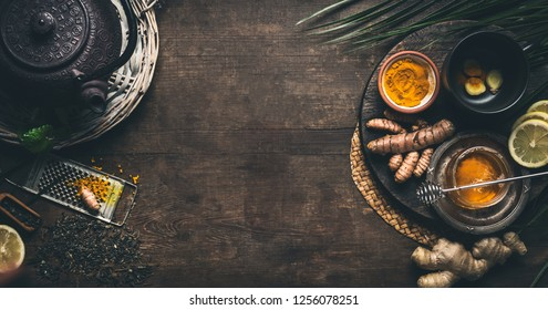 Herbal turmeric tea background. Cup of healthy turmeric spice tea with iron teapot and ingredients:  lemon,  ginger, cinnamon sticks and honey , top view frame with copy space. Immune boosting remedy
