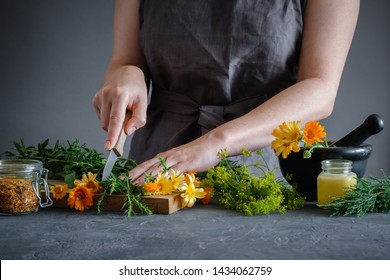 Herbalist woman chopping medicinal herbs with a knife to prepare healing medicines for treatment. Herbal medicine concept.