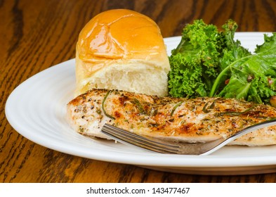 Herb-crusted baked chicken breast with kale and buttered roll