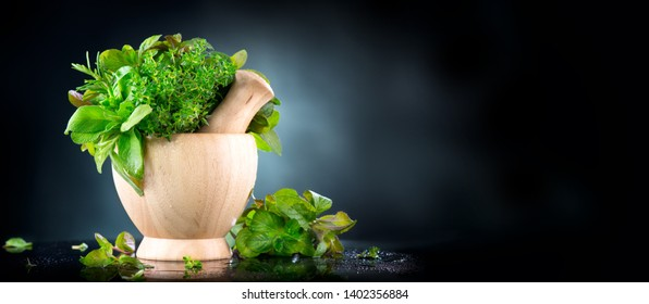Herbs. Bunch of Fresh green organic aromatic herb leaves in wooden mortar with pestle over black background. Mint, Peppermint, Rosemary, Thyme, Sage in bowl. Green leaf of fragrant Mediterranean Herb