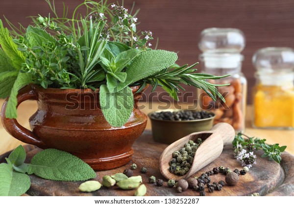 Herbs in a clay pot and spices on a wooden board.