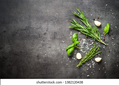 Herbs and condiments on black stone table. Rosemary, basil, thyme and garlic. Top view with copy space.