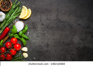 Herbs and condiments on black stone table. food cooking background. Rosemary, basil, thyme, lemon, sea salt and other. Top view with copy space.