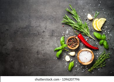 Herbs and condiments on black stone table. Rosemary, basil, thyme, lemon, sea salt and other. Top view with copy space.
