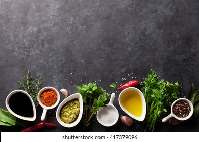 Herbs, condiments and spices on stone background. Olive oil and vinegar condiments. Mint, parsley and rosemary herbs. Salt, paprika and pepper spices. Top view with copy space