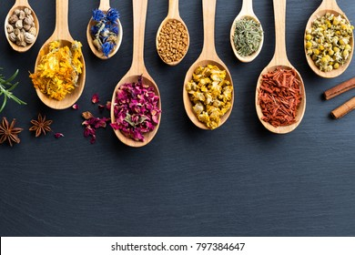 Herbs on spoons on a wooden background with copy space