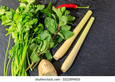 Herbs ready for cooking on a grey slate background.  Asian cooking.