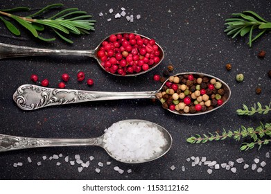 Herbs with salt and pepper in spoons on black slate stone background, top view, flat lay. Rosemary, thyme, salt and mixed peppercorns in vintage metal spoons.