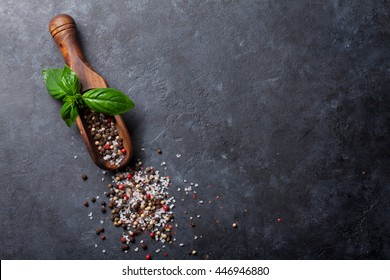 Herbs and spices. Basil, peppercorn and salt on stone kitchen table. Top view with copy space for your recipe