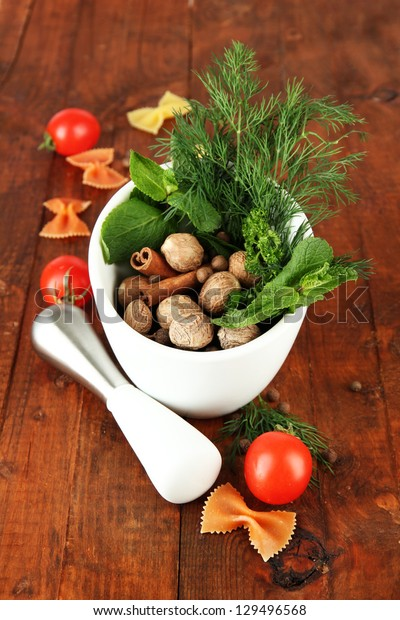Herbs and spices in ceramic mortar, on wooden background