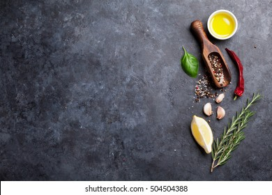 Herbs and spices. Cooking ingredients. Rosemary, basil, olive oil, salt and pepper. Top view over stone table with copy space for your recipe
