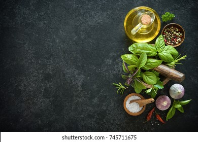 Herbs and spices on black stone table. Ingredients for cooking