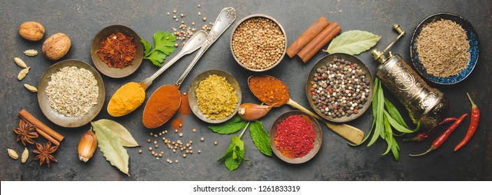 Herbs and spices on dark background, flat lay