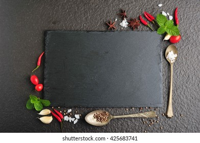 Herbs and spices over black stone background. Top view with copy space.