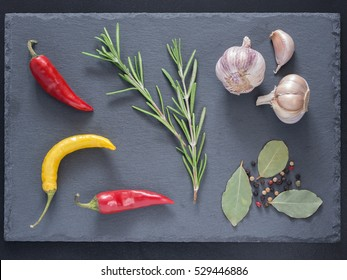 Herbs and spices over slate background. Top view or flat lay. Food background