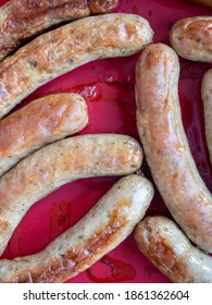 Herby sausages cooked in a red oven dish