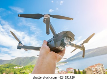 Herceg Novi, Montenegro, APRIL 18, 2017: Black drone quadrocopter in human hand against the background of sky and city