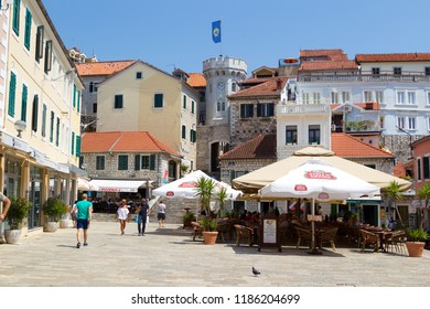 HERCEG NOVI, MONTENEGRO - August 1, 2018: the old town gate with the small clocktower surrounded by old houses, cafes and bars