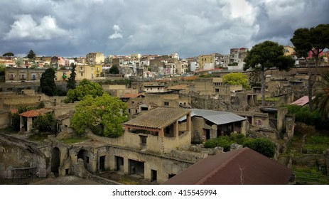 Herculane or Erculaneum City in Italy. Ancient roman city ruins and modern in background. The village was covered by ash at the eruption of Vesuvius volcano, still active in our days.