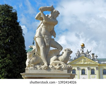 Hercules and the palace.  .  Hercules and the palace.  Białystok, Poland - May 03, 2019 A sculpture of Hercules fighting a dragon against the roof of the Branicki Palace in Bialystok.