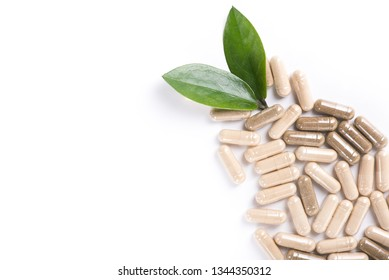 Herd medical pills and capsule with green leaves isolated on a white background. top view