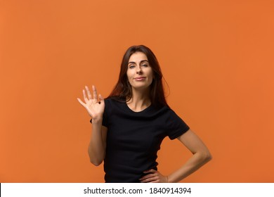 And here i am. Proud beautiful caucasian woman in black t-shirt smiles broadly and gives hello sign, shows by appearance that everybody waiting for her. Isolated over an orange background